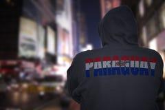 Опасное положение человека на улице города с черным hoodie с текстом Парагваем на его назад стоковое изображение rf