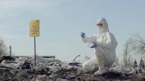Опасность радиации, virologist Hazmat в форму беря зараженный образец погани в пробирке для рассматривать на сбросе хлама сток-видео