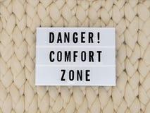 ОПАСНОСТЬ! Слово ЗОНЫ КОМФОРТА на lightbox на предпосылке knit Концепция зоны комфорта стоковое изображение