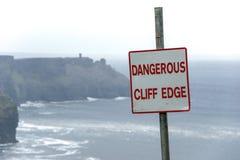Опасный край скалы подписывает внутри погоду overcast на скалах Moher в Ирландии Предупреждение знака опасности стоковое фото