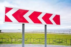 опасный поворот Дорожный знак в городе лета Стоковое Изображение