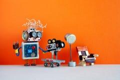 Оператор робота снимает киносъемк эпизод или фильм телевидения Смешной робототехнический оператор кинорежиссера с ретро камерой стоковое изображение