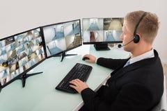 Оператор смотря множественный отснятый видеоматериал камеры Стоковое Изображение
