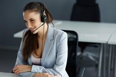 Оператор центра телефонного обслуживания сидя перед ее компьютером Стоковое Изображение