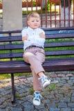 Опечален сиротливый мальчик, сидя на стенде Обиденный мальчик a стоковое изображение