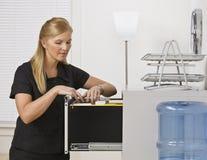 опиловка шкафа смотря женщину Стоковое Фото