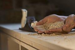 Опилк в руках на деревянной предпосылке Стоковые Изображения