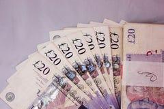Оплата платежей наличными денег фунтов английского языка зарабатывает ставридам туризма дохода валюты 20pounds свободу перемещени стоковое фото rf