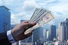 Оплатите доллар США на предпосылке городского пейзажа Стоковые Изображения