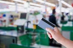 Оплачивать используя кредитную карточку на кассире проверки супермаркета Стоковое фото RF