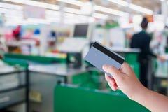 Оплачивать используя кредитную карточку на кассире проверки супермаркета Стоковое Фото