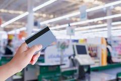 Оплачивать используя кредитную карточку на кассире проверки супермаркета Стоковая Фотография