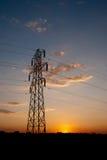 Опора электричества против померанцового захода солнца стоковые изображения rf