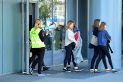 Опорожнение офисного здания Люди выходят из здания на входной двери стоковая фотография rf