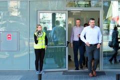 Опорожнение офисного здания Люди выходят из здания на входной двери стоковые изображения