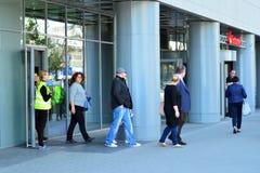 Опорожнение офисного здания Люди выходят из здания на входной двери стоковая фотография