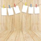Опорожните белые рамки фото вися с зажимками для белья на деревянной задней части Стоковая Фотография RF