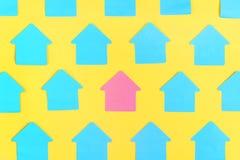 Опорожните голубые стикеры в форме дома, на яркой желтой предпосылке В центре розовый стикер пусто стоковое изображение