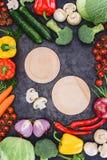 Опорожните деревянные плиты и свежие сырцовые овощи на черноте Стоковое Изображение