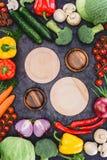 Опорожните деревянные плиты и свежие сырцовые органические овощи на черноте Стоковые Фото
