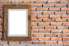 Опорожните деревянную смертную казнь через повешение картинной рамки на кирпичной стене Стоковые Изображения