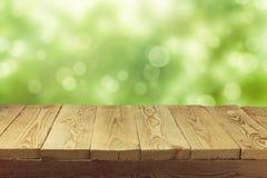 Опорожните деревянную таблицу палубы с предпосылкой bokeh листва Подготавливайте для монтажа дисплея продукта Стоковое Фото