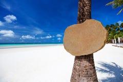 Опорожните деревянный шильдик на пальме на тропическом пляже Стоковые Изображения RF