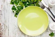 Опорожните зеленую плиту и свежую петрушку на деревенской белой деревянной предпосылке Стоковая Фотография