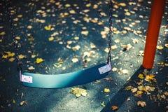 Опорожните качание для младенца или более старый ребенк на местной спортивной площадке и осени Стоковые Изображения RF