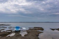 Опорожните каяк сидя на крае озера Стоковое Изображение RF