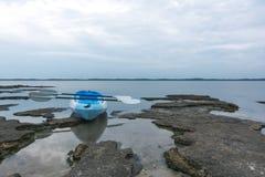 Опорожните каяк сидя на крае озера Стоковые Изображения RF