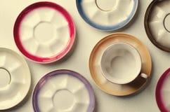 Опорожните красочные tableware, чашки и плиты фарфора на серой предпосылке тонизировано Стоковые Изображения RF