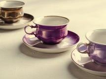 Опорожните красочные tableware, чашки и плиты фарфора на серой предпосылке тонизировано Стоковое Изображение