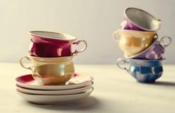 Опорожните красочные tableware, чашки и плиты фарфора на сирени, серой предпосылке Стоковые Изображения