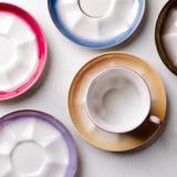 Опорожните красочные tableware, чашки и плиты фарфора на серой предпосылке Стоковые Фото