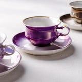 Опорожните красочные tableware, чашки и плиты фарфора на серой предпосылке Стоковая Фотография