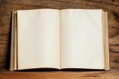 Опорожните открытую книгу на яркой деревянной полке на стене переклейки Стоковая Фотография