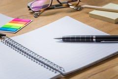 Опорожните открытый блокнот с ручкой и другие аксессуары на деревянные животики Стоковые Изображения RF