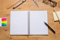 Опорожните открытый блокнот с ручкой и другие аксессуары на деревянные животики Стоковая Фотография