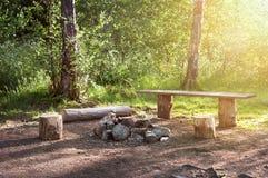 Опорожните располагаясь лагерем место в деревянной скамье леса и увольняйте место и таблица Туристский стоп Стоковое Изображение RF