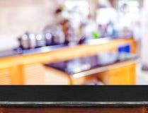 Опорожните черную мраморную столешницу и запачканный свет bokeh кухни внутри стоковая фотография