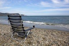 Опорожните sunbed с стеклом красного вина на пляже Стоковая Фотография