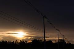 Опоры линии электропередач в вечере в сельской местности стоковое изображение