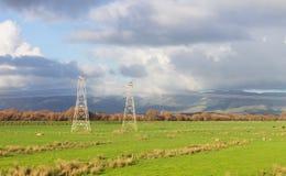Опоры стоя в электричестве нося открытой обрабатываемой земли Стоковая Фотография