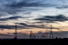 Опоры электричества на заходе солнца стоковые изображения
