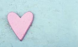 Определите розовое сердце на свете - голубой деревянной предпосылке Стоковые Изображения RF