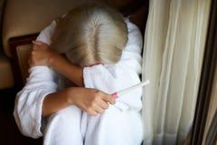 Определите унылую женщину жалуясь держащ тест на беременность сидя на кресле в живущей комнате дома стоковые изображения