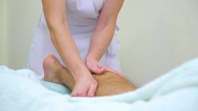 Опрокиньте вверх женского masseur массажируя волосатую голень молодого человека в салоне спа акции видеоматериалы