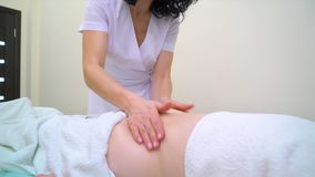 Опрокиньте вниз женского masseur в равномерном массажируя брюшке молодой женщины сток-видео