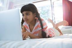Опрокиньте съемку девушки используя компьтер-книжку на кровати Стоковые Изображения